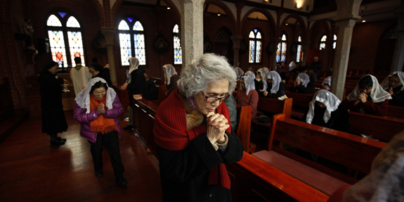 Woman prays during Mass at a Catholic church in Seoul